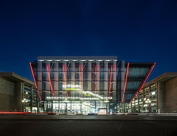 The exterior of the museum features a glass veil suspended by red columns, angled out over the street