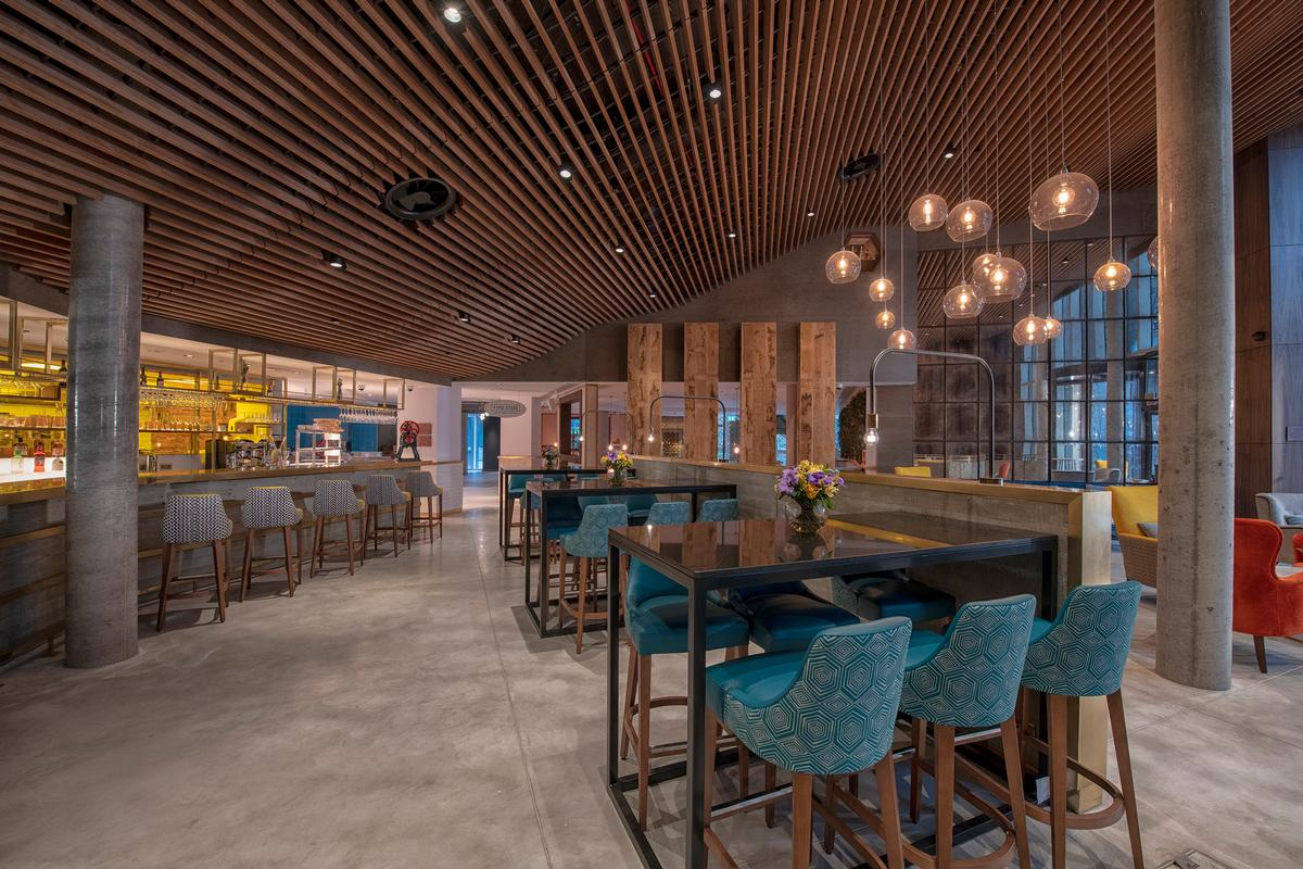 The hotel also boasts an on-site 'Food Store', a communal space which functions as a cafeteria, bar, and grocery. / Courtesy of Hilton Hotels