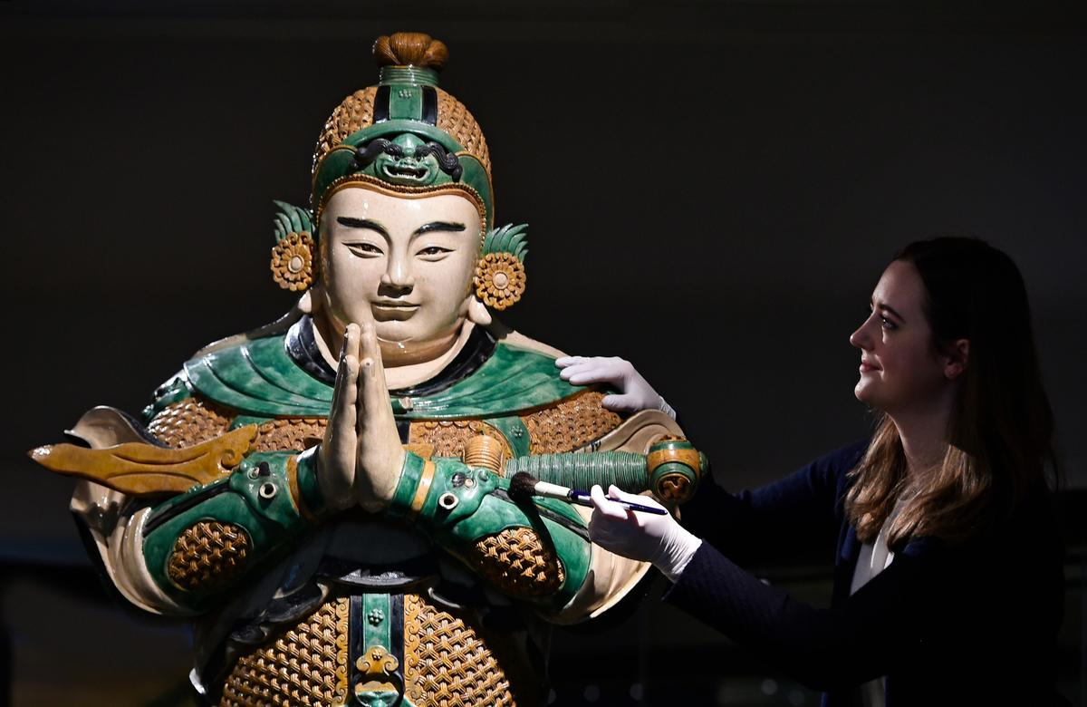 A museum conservator cleans a statue of Weituo, the leading guardian of Buddhist faith and teachings / Neil Hanna/NMS/PA