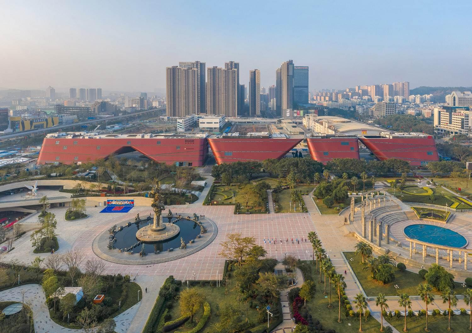 Longgang Cultural Centre is comprised of four angular red buildings, each housing one of its four main elements. / Courtesy of Mecanoo