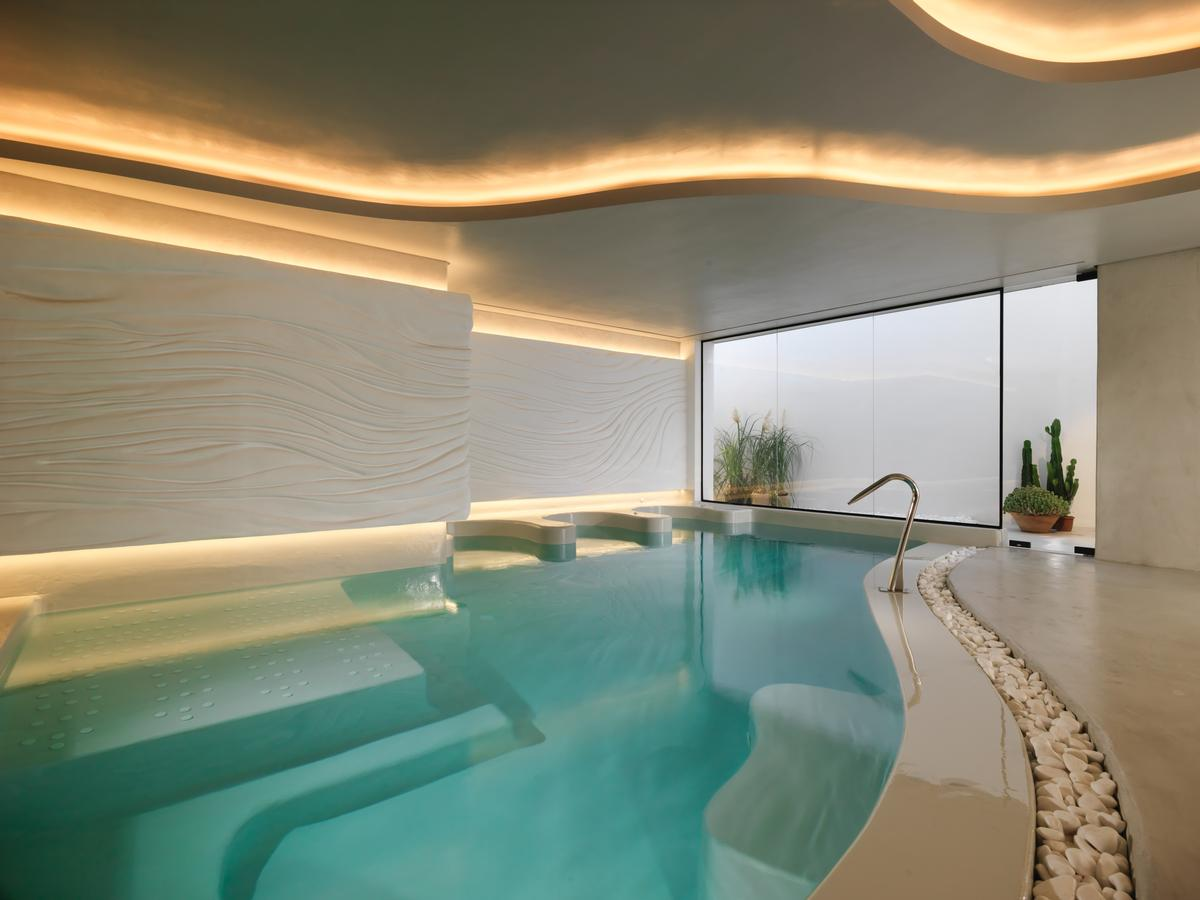 Wellness and leisure amenities include pools, a spa, a hammam, a sauna, and an outdoor garden. / Courtesy of Niall Clutton