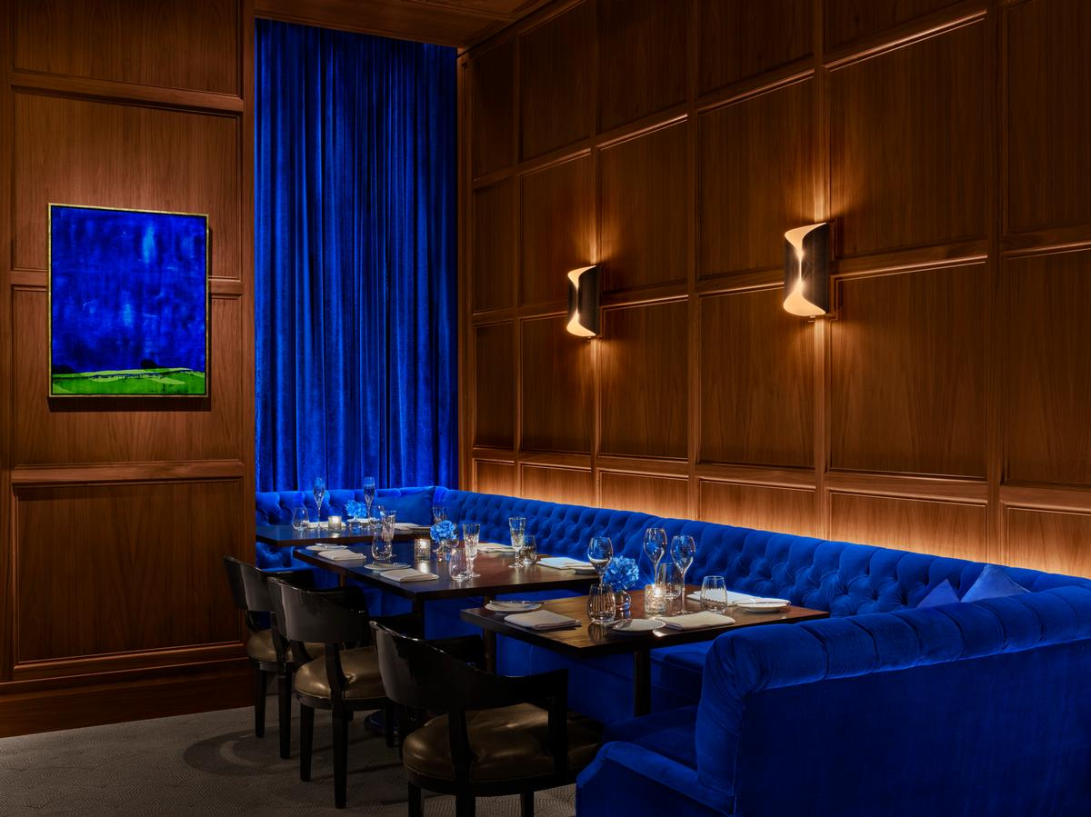 The restaurant's interior spaces are furnished with electric blue and emerald green banquettes. / Photo by Nicholas Koenig