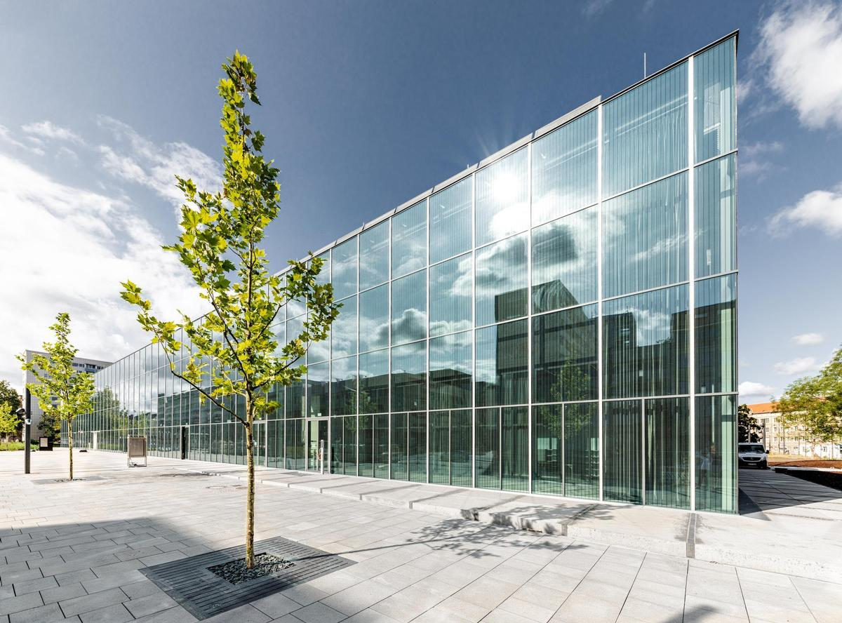 In the daytime view, the Black Box is less obvious, while the glass façade reflects nearby trees and buildings / Stiftung Bauhaus Dessau / Hartmut Boesener, 2019