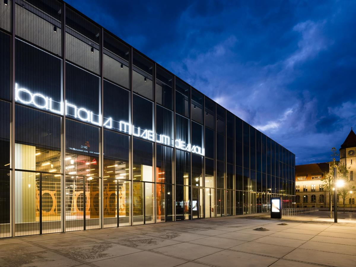 A night-time view of the museum, with the interior Black Box visible above the ground floor / Stiftung Bauhaus Dessau / Thomas Meyer / Ostkreuz, 2019