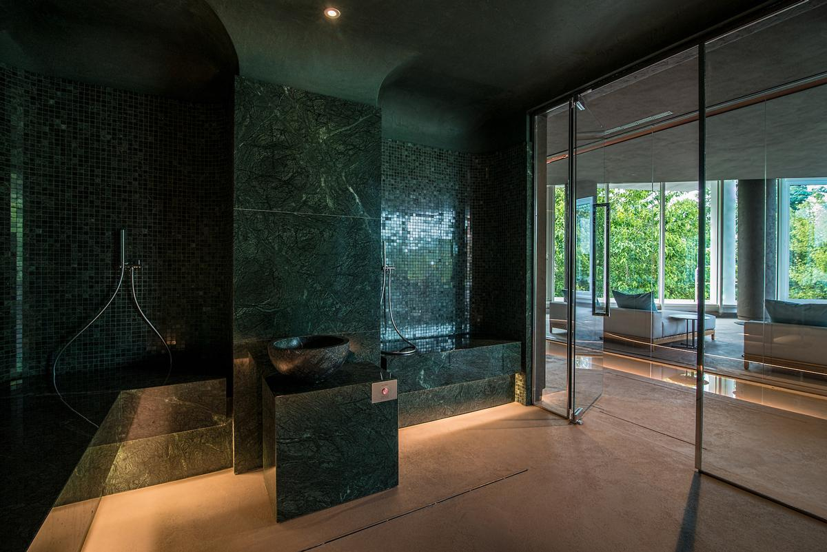 The hammam, completely made in Guatemala Green marble, features a large glass front wall / Chiara Grossi