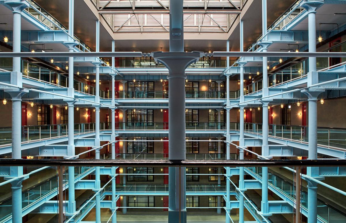 The atrium spans six storeys to a central glass roof / Native