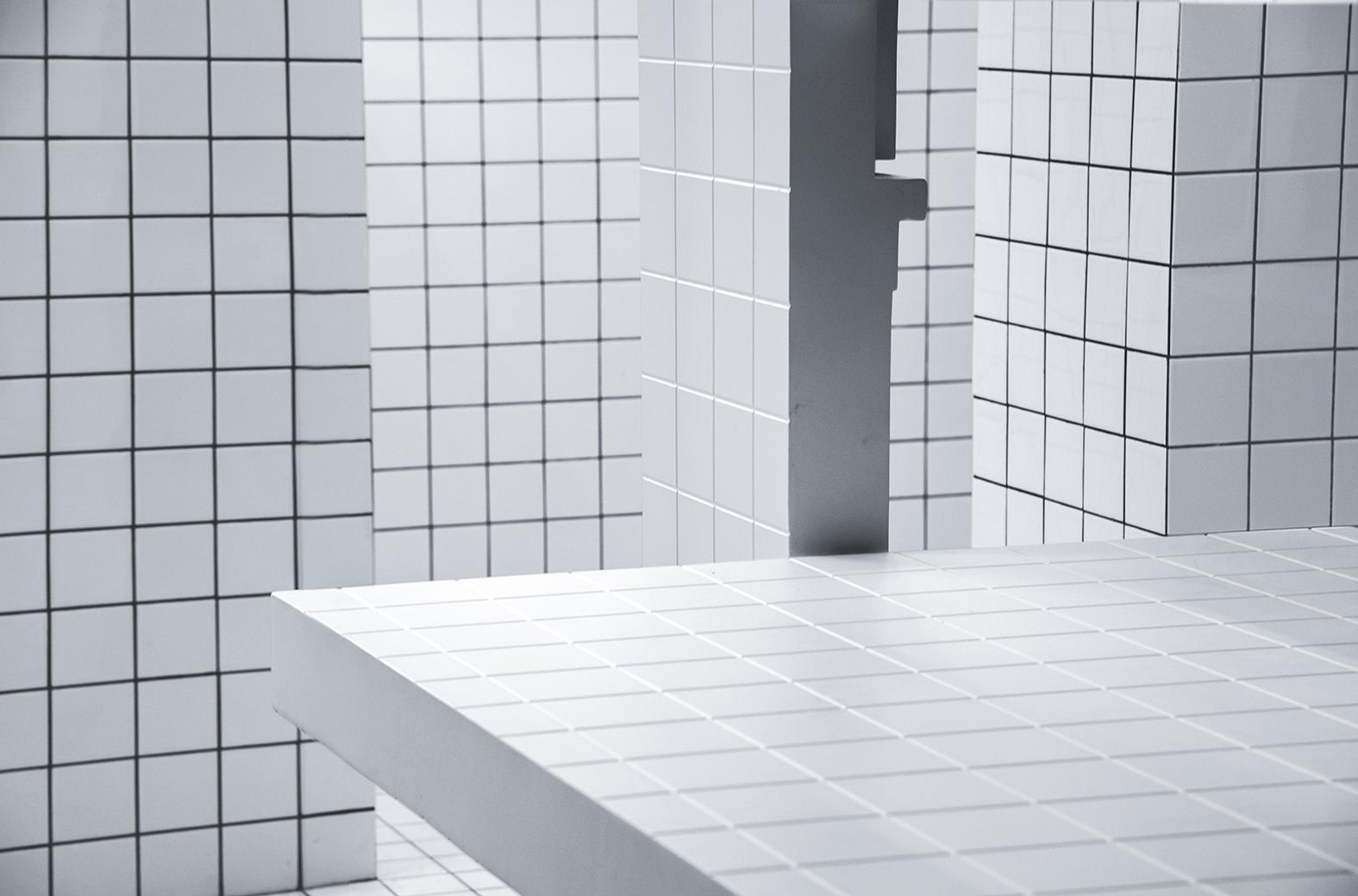 The floors, walls, and counter are covered in a white, tiled grid graphi / Unknown Works
