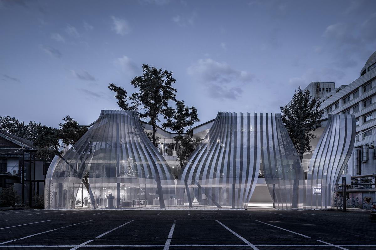 The translucent façade is illuminated at night revealing elements hidden behind it / Jin Weiqi