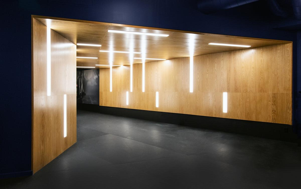 The workout space employs a warm, dark pallette juxtaposed with bright lighting and highlights / Rafael Soldi