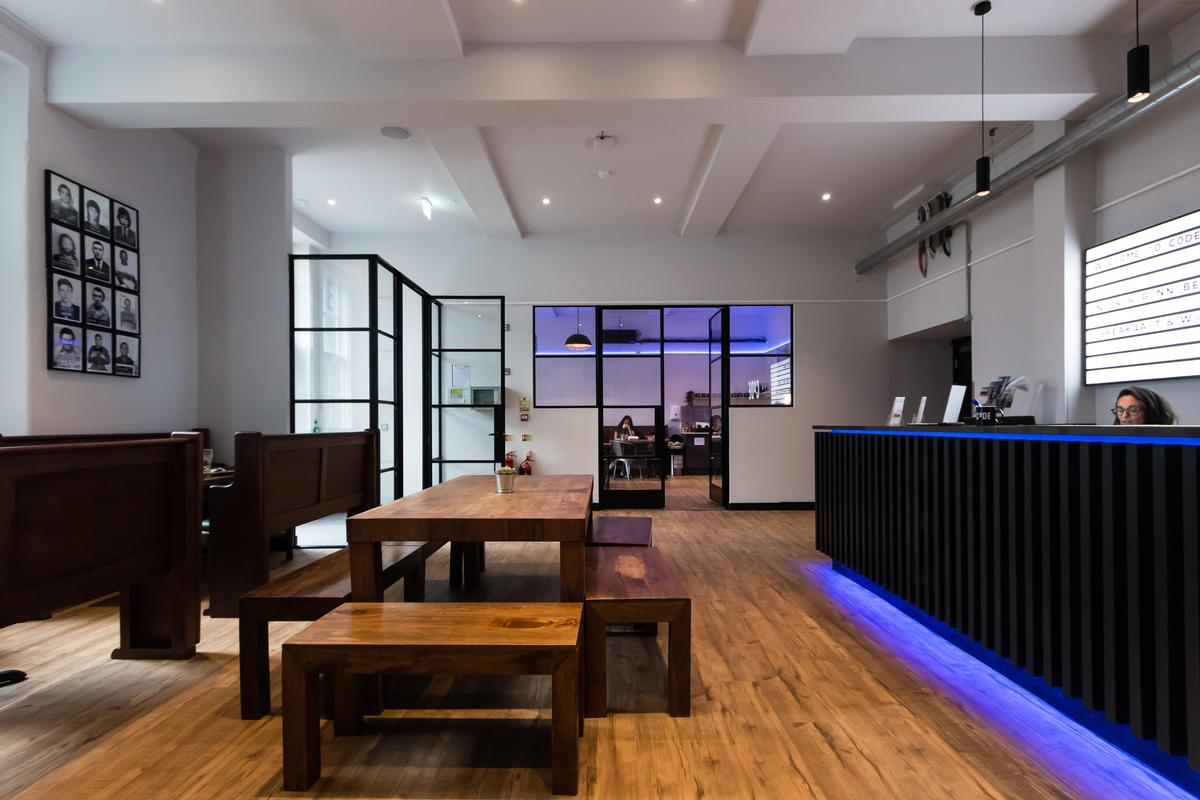The entrance foyer and breakfast room use the original courtroom bench seating / Code Pod Hostels