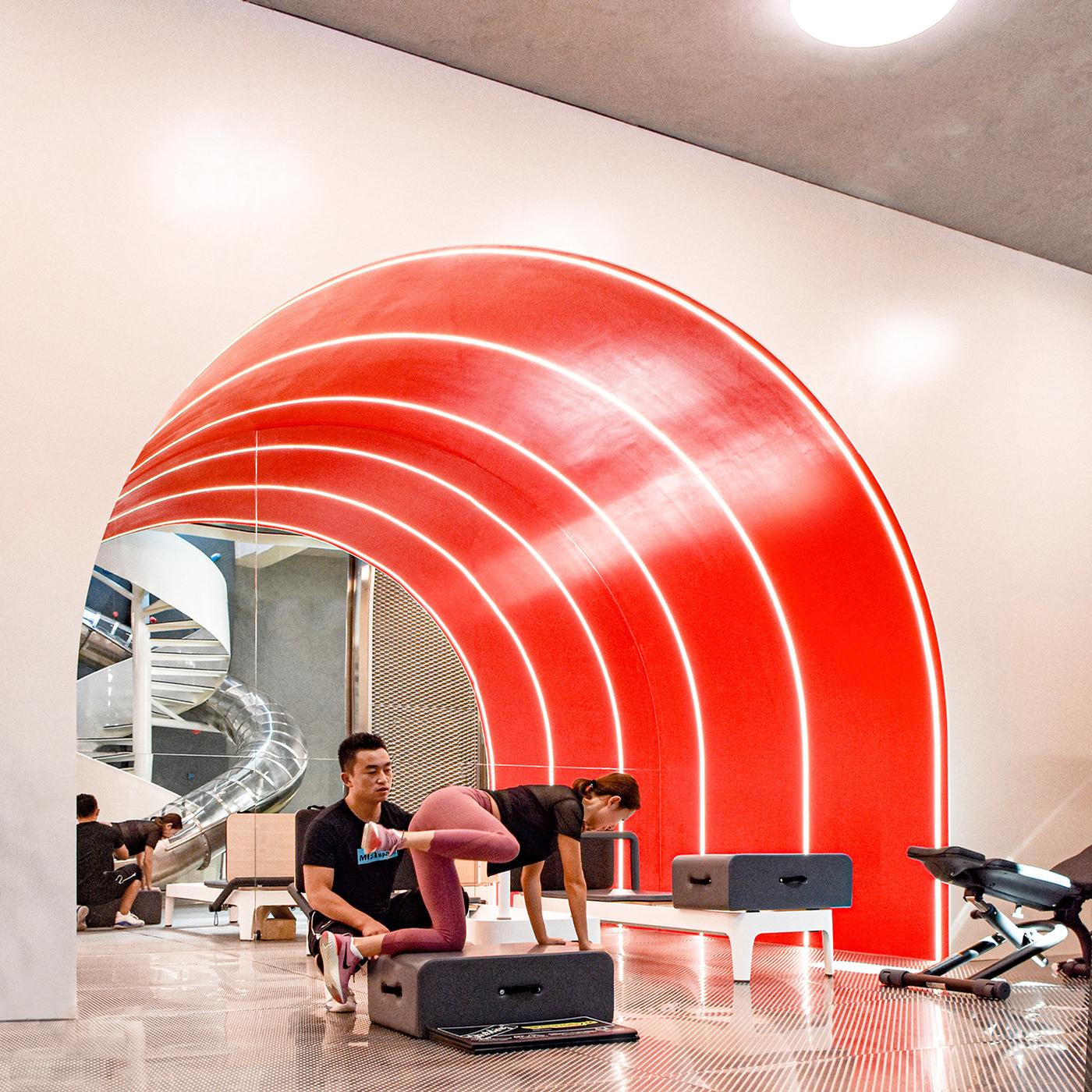 A red arch with embedded light-strips connects two spaces within the gym