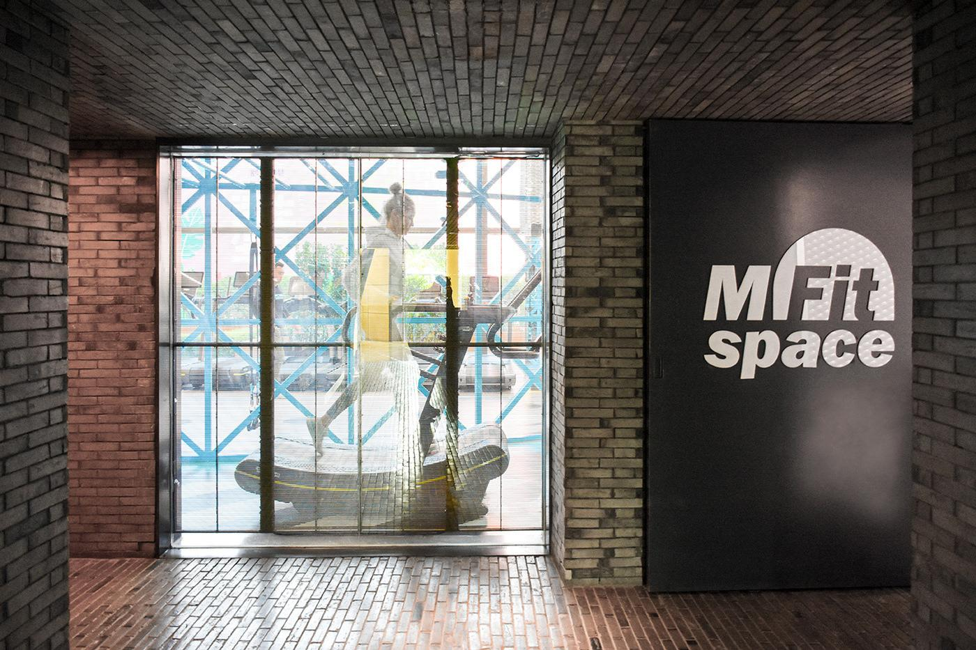 A semi-permeable partition gives visitors a glimpse into the gym as they enter