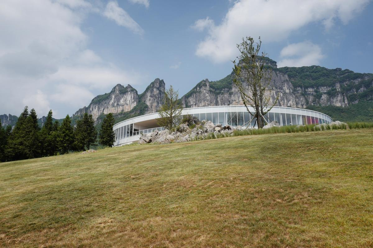 Its white elliptical form stands out against the surrounding green hills / C+ Architects