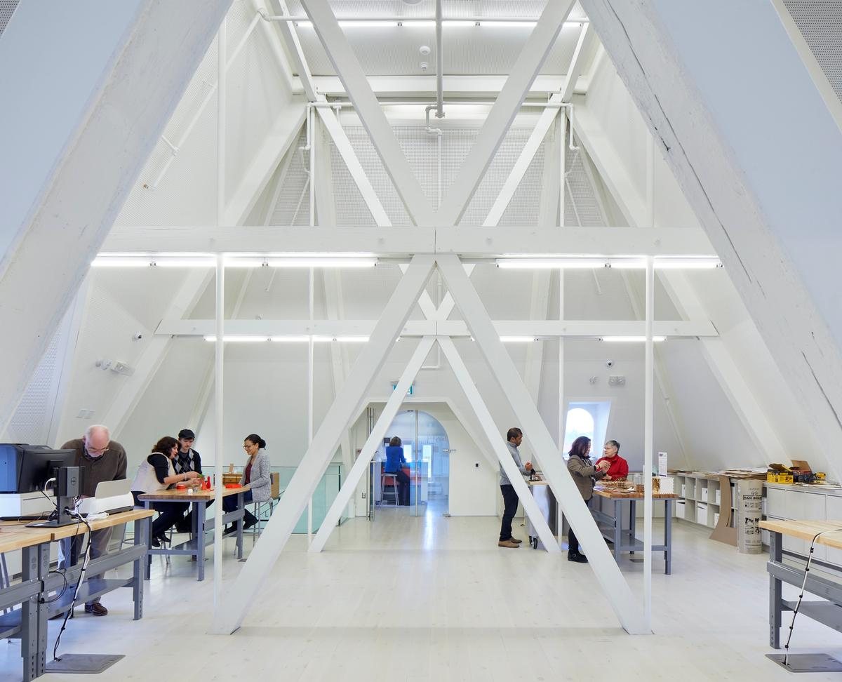 A makerspace in the peaked attic is braced by steel trusses / Tom Arban