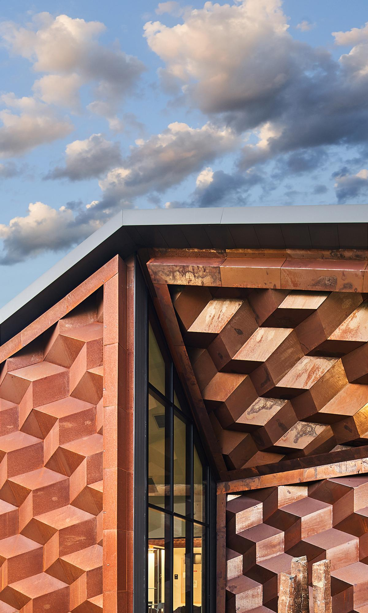 In addition, angled sections are cut out of the building's ends and their façades covered in raised, diamond-shaped panels / Hufft
