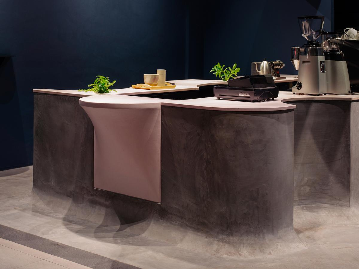 The base of the counter is cast in concrete and is designed to merge into the floor / Khoo Guo Jie