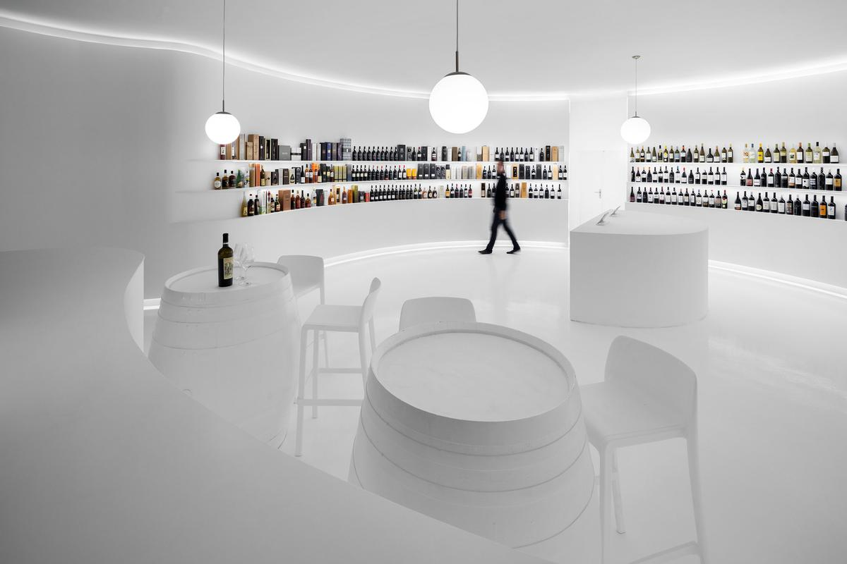 A simple tasting zone comprises two wooden barrels and some chairs / Ivo Tavares Studio