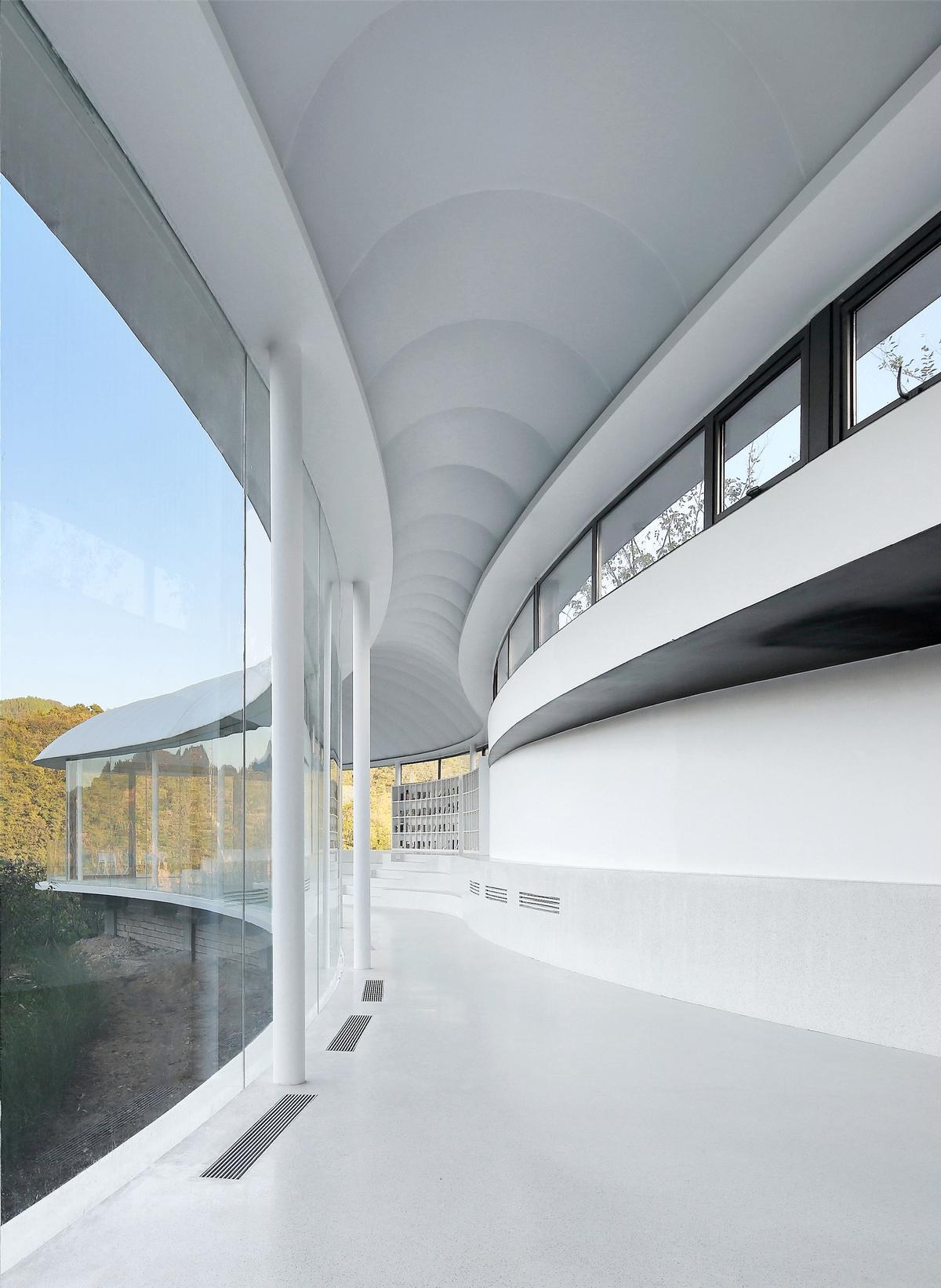 The building curves with the shape of the mountain to create two bulbous ends joined by a thinner midriff / Jin Xiaowen