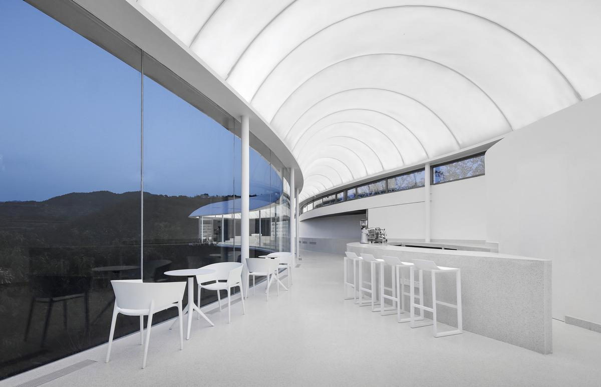 The interior continues the cloud-white theme of the building / Jin Xiaowen