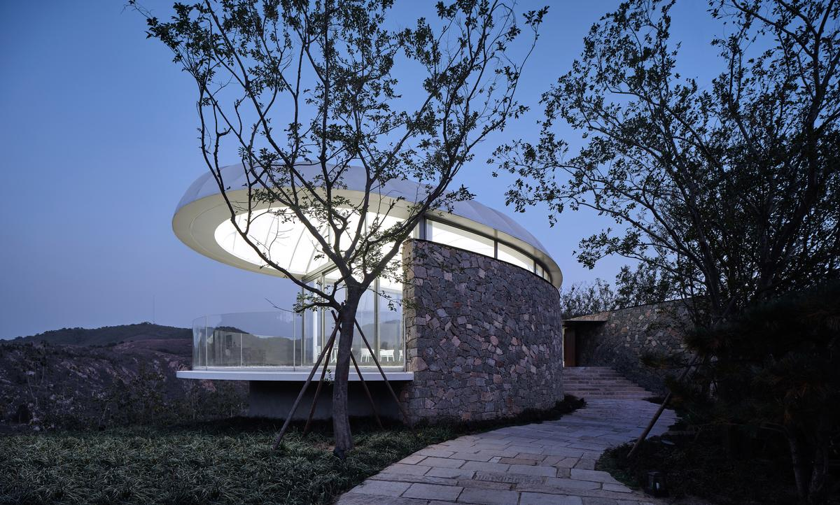 The building is constructed on a stone plinth and has a stone wall running along one of its sides / zystudio