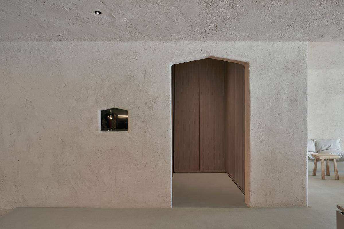 Clay walls are left plain, recalling the utilitarian nature of a horse stall / Oculis Project