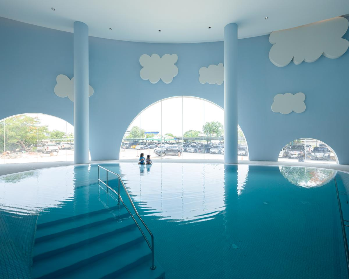 There is a swimming pool with artificial clouds floating above it / Ketsiree Wongwan