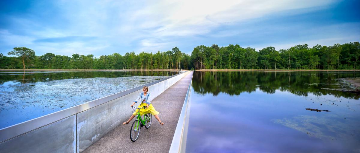 Cycling through Water takes the form of a sunken cycle path run through a lake / VisitLimburg.be