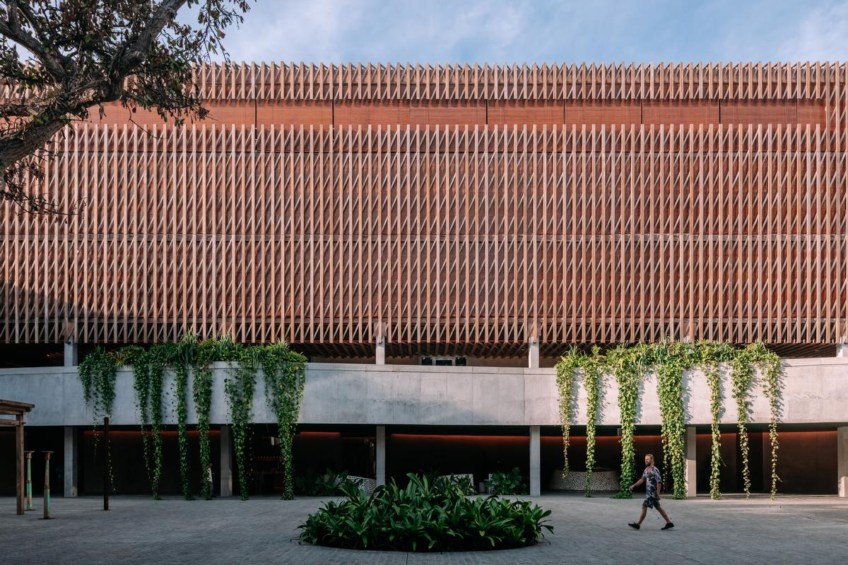 The building has a square layout and is constructed from a mix of open brickwork and timber cladding / Kevin Mak