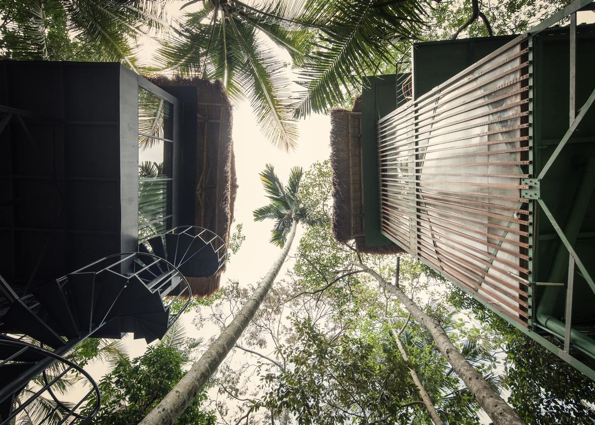 The hotel is a mix of part-industrial, part-natural structures in a tropical forest setting / kiearch