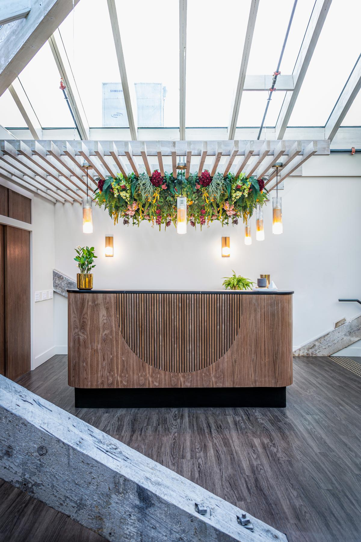 The reception desk features a floaral installation / James Jones