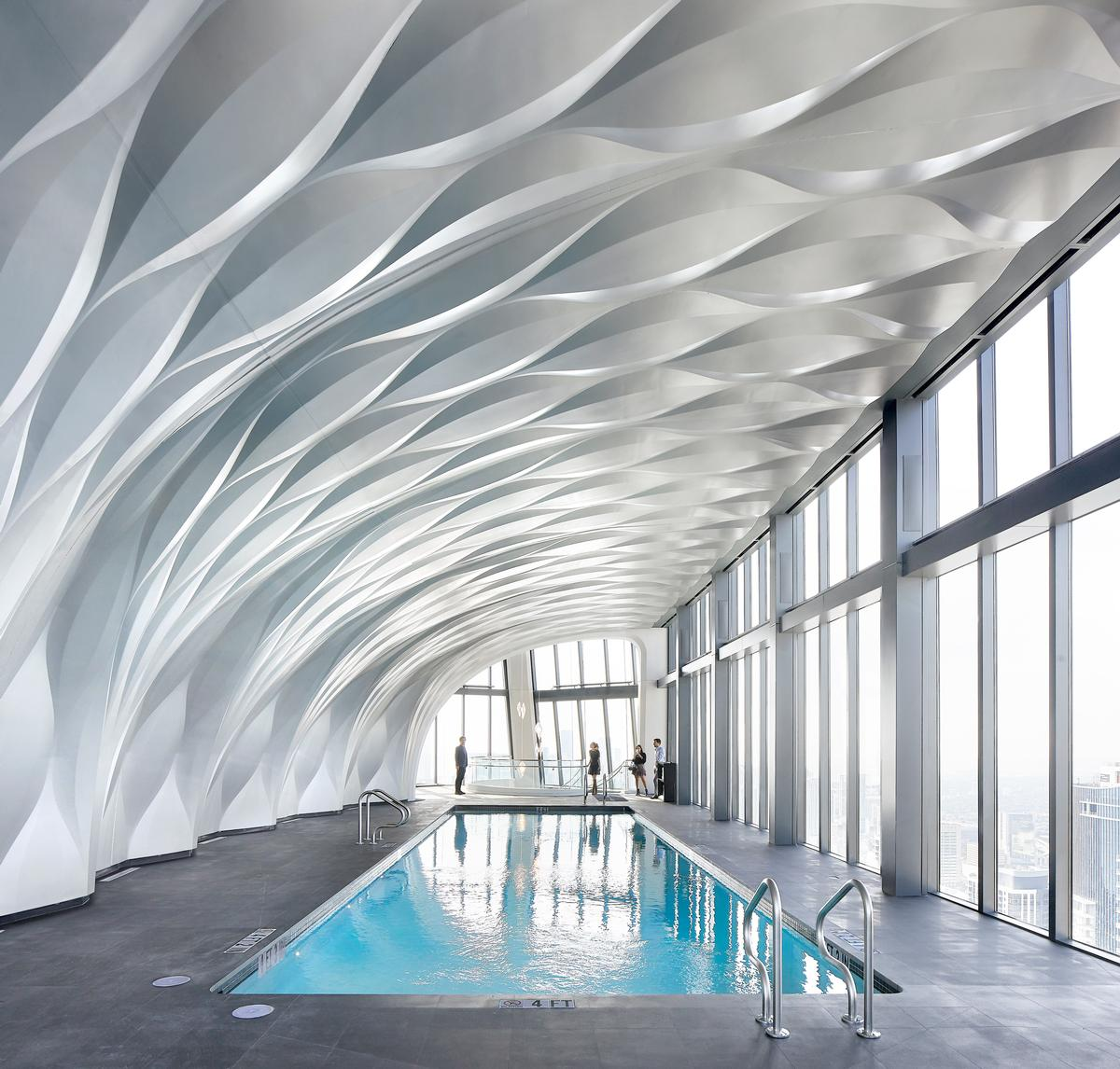 A double-height aquatics centre features an infinity pool / Hufton+Crow