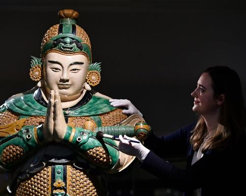 A museum conservator cleans a statue of Weituo, the leading guardian of Buddhist faith and teachings