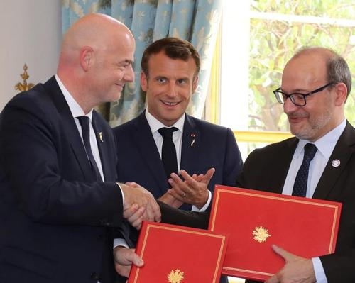 FIFA president Gianni Infantino (left) and AFD chief executive Remy Rioux (right) sign agreement at a ceremony attended by French President Emmanuel Macron (middle) / FIFA