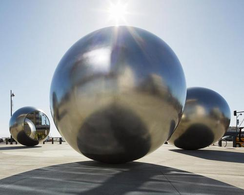 The artwork consists of five polished, hydroformed steel orbs